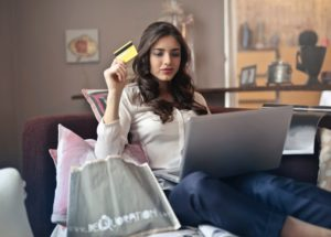 woman shopping online with credit card from couch
